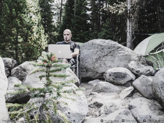 Chris Behnke working in the woods on a laptop :-)